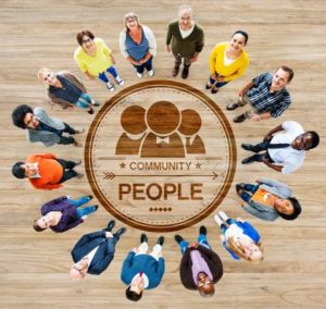 Diverse group of people standing around a circular image with the words 'people' and 'community' looking up at the camera